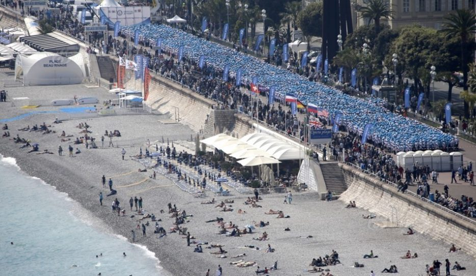 Employees of the TIENS Group, a Chinese company, attend a parade organized by CEO Li Jinyuan as part of a four-day celebration weekend for the 20th anniversary of his company, on the Promenade des Anglais, Nice, southeastern France, Friday, May 8, 2015. Li Jinyuan is sending off half his team about 6,400 employees on a two-day trip to Paris and two-day trip in Nice, France. (AP Photo/Lionel Cironneau)